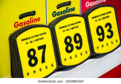 Close up on Octane rating and high prices at the gas pump. Yellow buttons to choose your poison and unleaded or premium gasoline. Fossil fuels power our cars and transportation and cost is rising