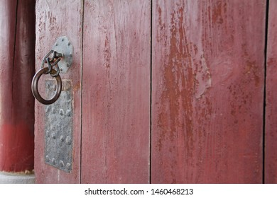 Close up on a old lock gate and chain on red wooden gate.Vintage red wooden door with metallic doorhandle and old chain.