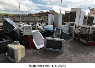 Close up on old Television sets and old fridge units at a electonic waste collection site