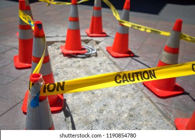 Close up on an orange construction cone with yellow caution tape, at a sidewalk construction site near the shop.