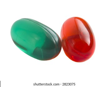 a close up on orange and green pills isolated on a white background