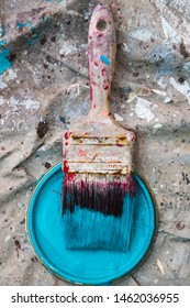 Close up on paint brush and teal paint
