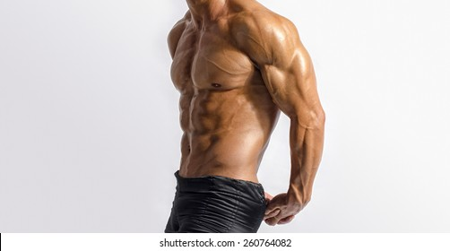Close up on perfect abs. Strong bodybuilder with six pack.Strong bodybuilder man with perfect abs, shoulders,biceps, triceps and chest, personal fitness trainer flexing his muscles