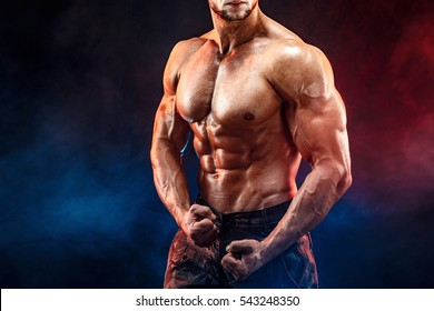 Close up on perfect abs. Strong bodybuilder with six pack. Man with perfect abs, shoulders,biceps, triceps and chest, personal fitness trainer flexing his muscles in blue, red smoke