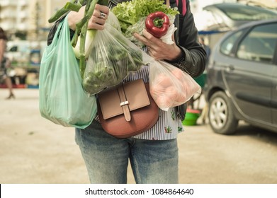 Close up on person buyer hold groceries in bags. Buy sell process. Choosing healthy wellbeing lifestyle, vegetables background
