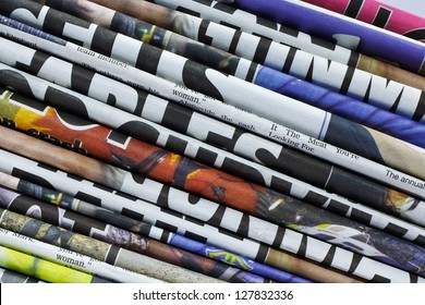 close up on a pile of differnt color newspaper titles