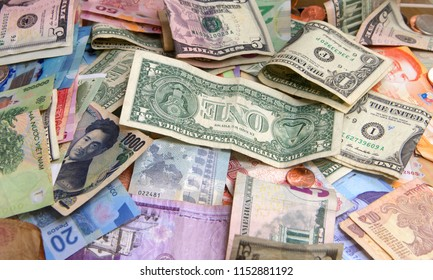 Close up on pile of many bank notes from various countries from around the world. U.S., German, Swiss, Canadian, Brazilian, Vietnamese, Mexican. Many countries represented in currency. Bills and coins