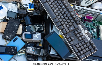 Close up on pile of mixed electronic waste, old broken computer parts and cell phones