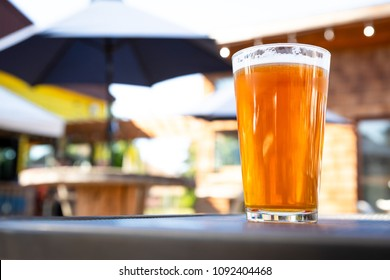 Close up on a pint glass of Amber Ale beer, at an outdoor patio of a craft brewery, with space for text on the left
