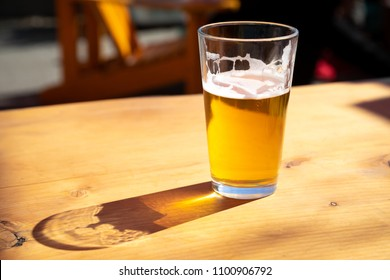 Close up on a pint glass of amber Pale Ale beer, casting a shadow on a wood table, and space for text on the left