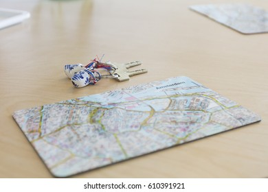 close up on place mat with a touristic map of Amsterdam city center and a set of keys on a Dutch wooden shoes key ring