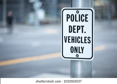 Close up on a Police Department Vehicles Only parking sign, on a metal light post, with a blurry city background