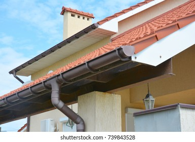 Close up on rain gutter pipeline system with holders and gutter downspout pipe. Residential house  roof gutter.