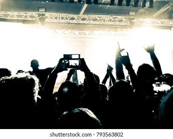 Close up on raised hands filming a concert on smart phone.