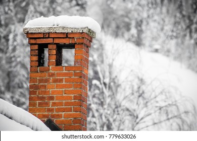 close up on red brick chimney in winter scenery with snow on a rooftop