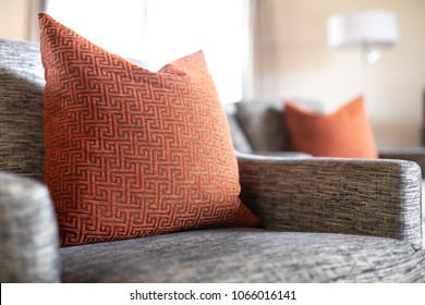 Close up on a red geometric pattern throw pillow on a gray cushioned couch in a row of chairs, with a living room scene in the blurry background, and space for text on the right