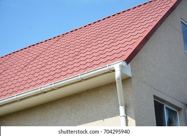 Close up on red metal roof with white, plastic rain gutter system. Roofing Construction.