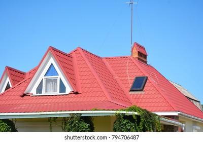 Close up on red metal roof with mansard, skylight window, roof guttering pipeline system problem area.