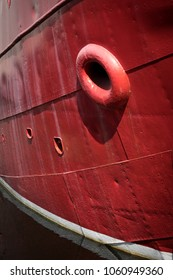 Close up on the red steel hull of a tugboat or firefighting boat, in calm harbor water