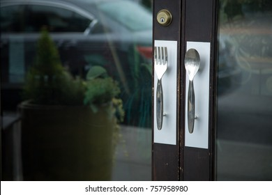 Close up on a restaurant entryway, with fork and spoon handles as door knobs