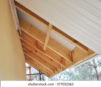 Close up on Roofing Construction. Soffit and Fascia Installation. is Usually Constructed of Vinyl, Wood or Aluminum and is Installed on the Underside of Roof Overhangs and Eaves.