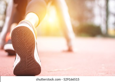 Close up on running shoe of a young man having runner stretching before the run - Athlete preparing position to start a run