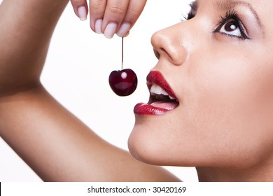 close up on of a sensual girl playing with her mouth with a cherry