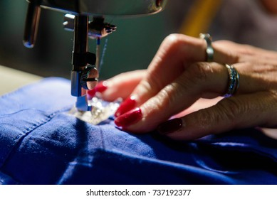 Close up on sewing machine and seamstress' hands while she is working