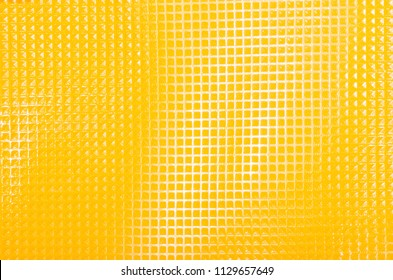 Close up on shiny plastic texture. Yellow squared surface as a background.