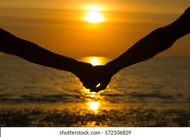 Close up on silhouette of couple's arms holding hands at sunset by the sea to celebrate Valentines Day in the island of Koh Phangan, Thailand. Romantic honeymoon, love concept