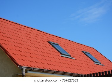 Close up on Skylight Attic Windows with Red Metal House Roof. Modern Home Attic Skylight Waterproofing.