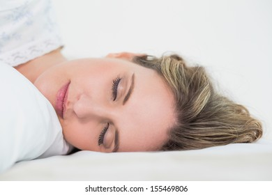 Close up on sleeping pretty blonde woman in cosy bedroom