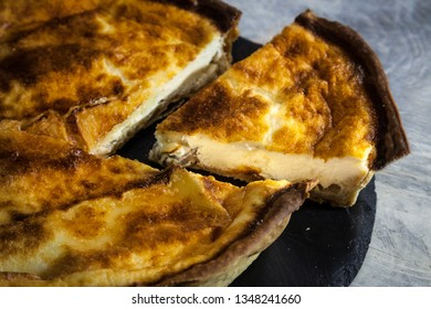 Close up on a slice cut of a Traditional French Quiche Lorraine pie on display on a rustic wooden table. It is an iconic dish of Eastern France, a pastry made of flan, cheese, milk, cream and ham