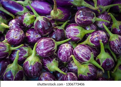 Close up on small round purple eggplants for sale at a farmers market