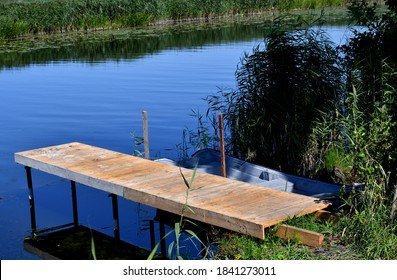 A close up on a small wooden pier or platform made out of logs, boards, and planks with a small boat or fishing vessel safely parked nearby next to a reed and grass covered coast seen in Poland