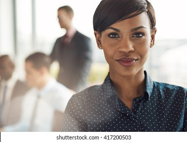 Close up on smiling beautiful business woman with light flare over shoulder from large window in office with group
