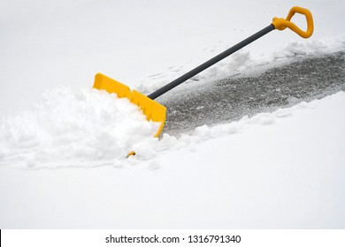 close up on snow shovel removing snow on the driveway