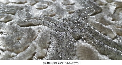 A close up on a specific spot of a silvery beautiful sajadah (prayer rug). Focusing on the center of an emerged groove.