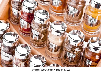A close up on a spice rack full of a variety of different spices and herb  isolated on a white background.