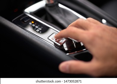 Close up on the Sport Mode button of a car. Finger pressing the button.
