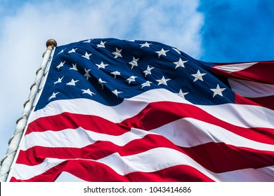 Close up on stars huge American Flag waving in the breeze with the perfect blue sky background. patriotic symbol of the United States of American one nation under god with liberty and justice for all
