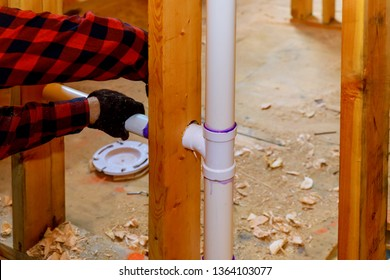 Close up on t joint and pipes for a home sewage system, in wood wall, drain and vent plumbing system
