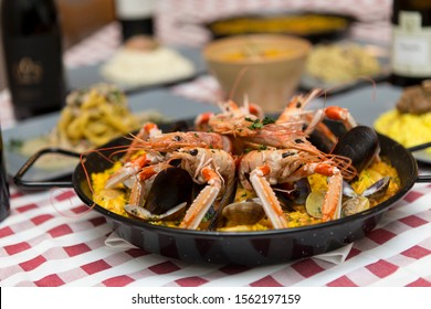 Close up on a table prepared for lunch, a metal pot with spanish Paella decorated with prawns is visible, background is a defocused seafood restaurant table with other dishes