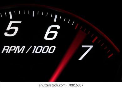 Close up on a tachometer reaching maximum engine speed