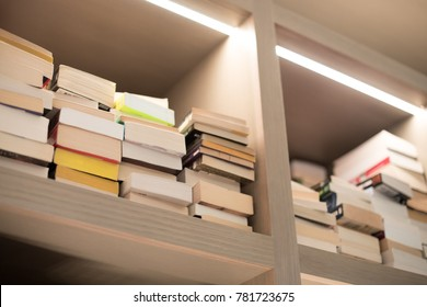 Close up on a tall white wood bookshelf, lined by stacks of paperback books