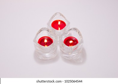 Close up on three red scented candles in a jar with flame on a white background