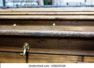 Close up on top edge of old long wooden church pews with brass hooks on the side with copy space
