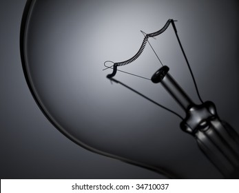 Close up on a transparent light bulb over a grey background.