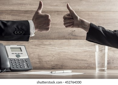 Close up on two hands with thumbs up near telephone, signed contract and glass of water for concept about business negotiation or closing sales.
