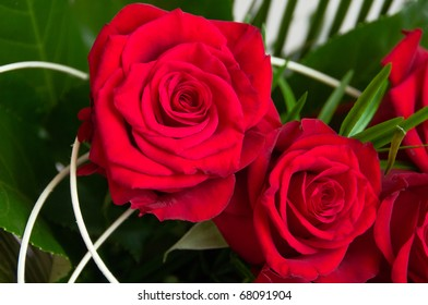 Close up on two romantic red roses in the decorative bouquet